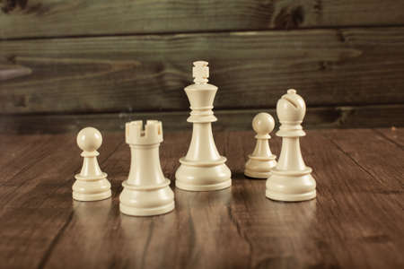 White chess figures on a wooden desk Stock Photo