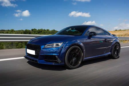 Blue luxury sedan car on the highway