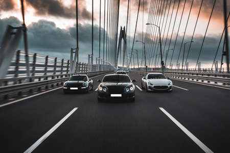 Sport casr driving on the bridge, front view
