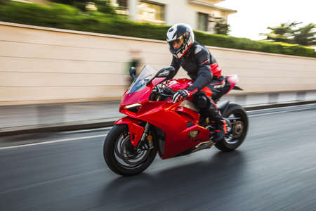 Biker driving a red motorcycle in helmet and gear