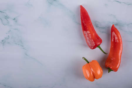 Three chili peppers on a blue marble table