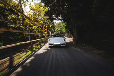 White cabriolet high speed drive in the forest