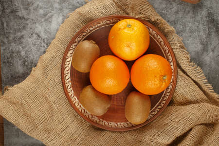 Orange and kiwies in a pottery bowl. Top view.