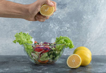 Man squeezing lemon to plate of vegetable salad Banque d'images