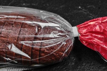 Sliced black rye bread in plastic bag on dark background