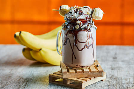 Chocolate smoothie with choco syrup and branch of bananas