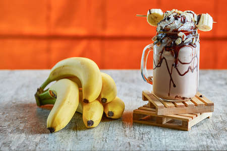Banana milk shake with cream, chocolate and branch of bananas on the marble background Zdjęcie Seryjne