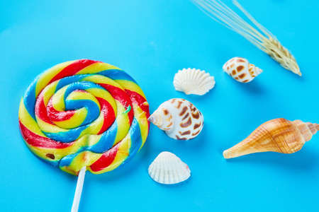 Colorful lollipops with seashells on blue background