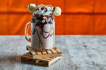 Chocolate smoothie with choco syrup, banana and whipped cream on the wooden board in the bright background Zdjęcie Seryjne