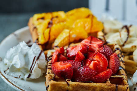 Waffles with ice-cream, banana, strawberry, chocolate in the white plate on the marble background