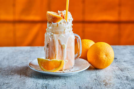 Orange smoothie with sprinkles and straw on the white plate