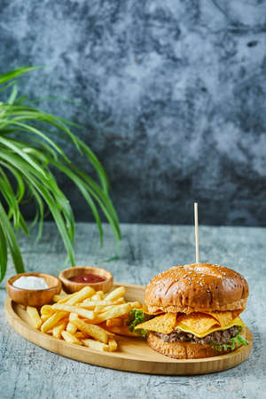 Big burger with fry potato in the wooden plate on the marble background