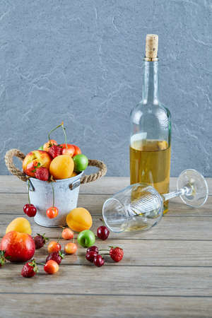 Bucket of fresh summer fruits, bottle of white wine and empty glass on wooden table