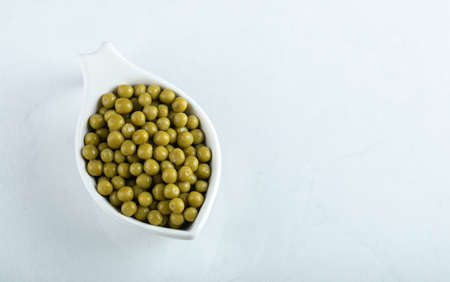 Top view of green olives in white bowl