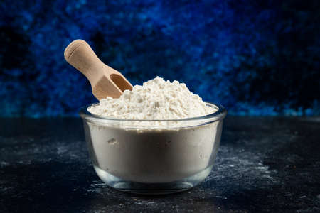 Glass bowl of flour on blue background