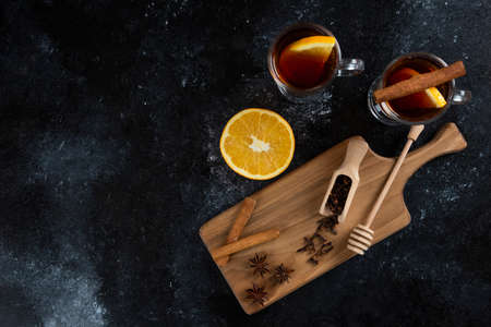 Two glass cups of tea and with cinnamon sticks and wooden dipper