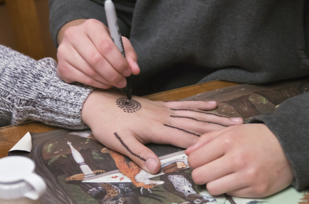 A young lady uses a pen to draw a design on the hand of a girl in a house in Deep Creek Lake,Maryland