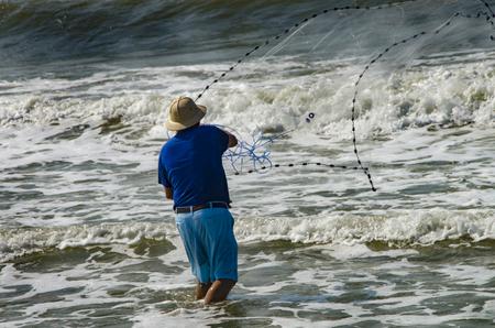 A fisherman cast a bait nes into the surf at Emerald Isle ,Norht Carolina