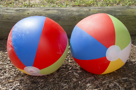 Beach balls waiting laying on a playground ready for use