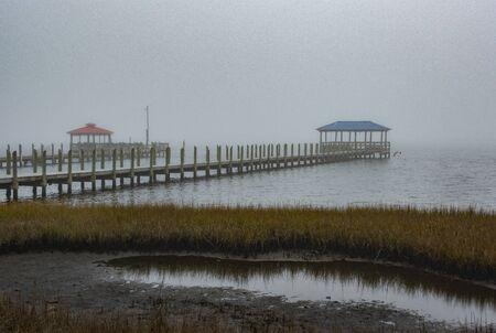 Fog shrouds the pier at the goose creek Campground near Emerald Isle, North Carolina Reklamní fotografie