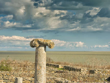 Dramatic blue sky with white clouds over the ruins of an ancient greek column at Histria, on the shores of Black Sea. Histria is the oldest urban settlement on Romanian territory Stock Photo