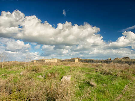Dramatic blue sky with white clouds over the ruins of the ancient greek colony of Histria, on the shores of Black Sea. Histria is the oldest urban settlement on Romanian territory