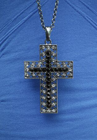 Close-up of cross necklace on a blue shirt.
