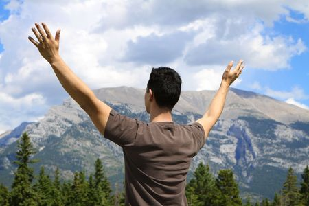 Man standing in nature with arms lifted up photo