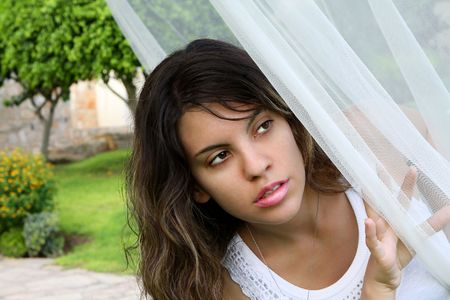 Attractive and beautiful young girl with a neutral facial expression hiding and peeking through a semi-transparent white curtain veil Stock Photo - 7583589