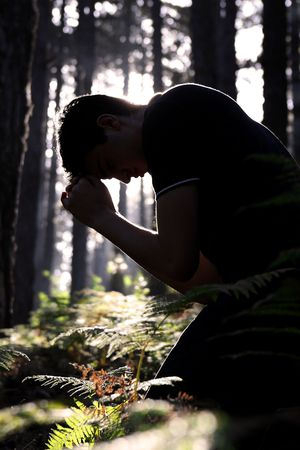 Silhouette of a man kneeling and praying in the forest