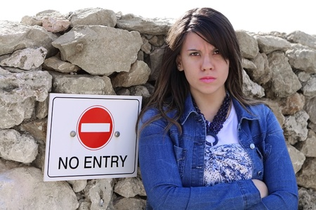 Cute upset girl standing by NO ENTRY sign, expandable white top for text Stock Photo