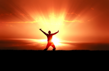 worship praise: Silhouette of  jumping man in field of grass, bright sun behind
