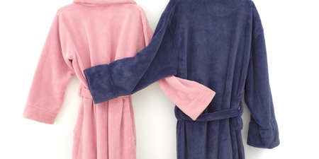 Snuggling blue and pink bathrobes with arms around each other, isolated on white