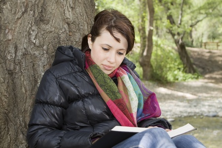 3/4 view of girl sitting and reading a book by a tree Stock Photo