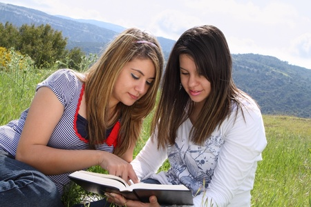 Two girls sitting in nature reading together Stock Photo - 9540385