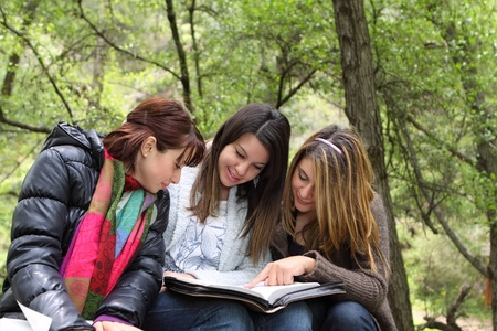 Three girls sitting in forest reading together