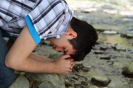 Close-up of man kneeling and praying by a creek Stock Photo - 9540382
