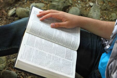 Man reading Bible, close up of Bible and hand photo