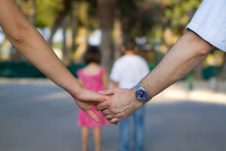 Close up of holding hands, two kids in background Stock Photo