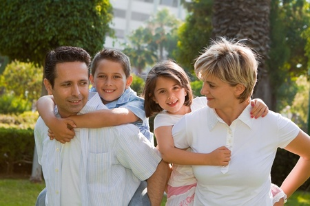 Two parents giving piggyback rides to two children photo