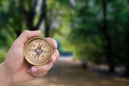crossroad guide: Male hand holding old compass. Stock Photo