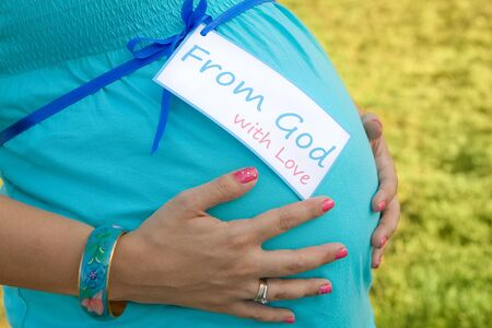 Expecting Mom's hands on tummy with card