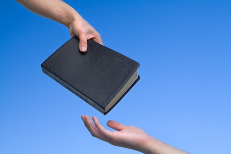 Hand giving the Bible to another person over blue sky