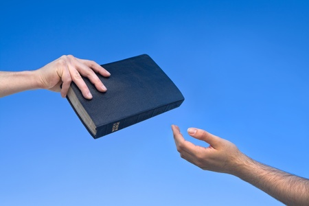 Hand giving the Bible to another person Stock Photo