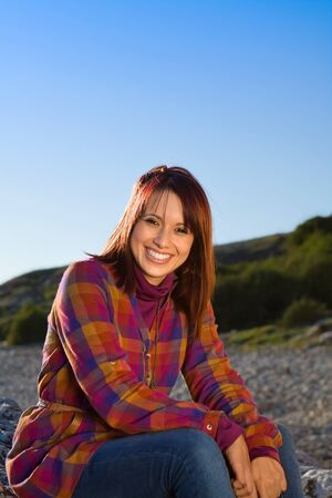 Friendly girl smiling and sitting casually Stock Photo - 13809437