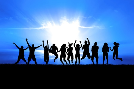 praise: Silhouettes of a celebratory group jump in field of grass, bright sun behind