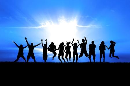 alabanza: Siluetas de un grupo de salto de celebración en el campo de hierba, el sol brillante detrás de Foto de archivo