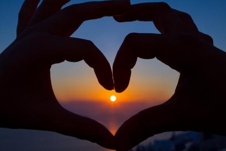 haciendo el amor: Dos manos hacen un corazón en la puesta del sol Foto de archivo