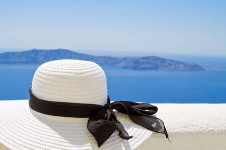 Sun hat on a ledge with ocean background Stock Photo
