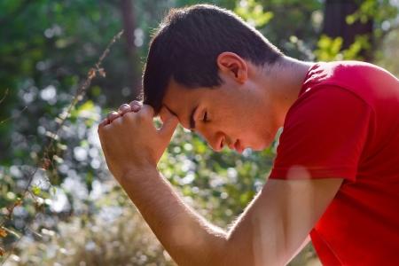 Giovane uomo in ginocchio e pregare nella foresta Archivio Fotografico